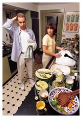 Man and woman in kitchen seeming to be having an argument.